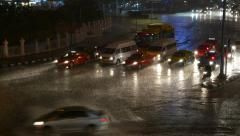 Cars wait passing traffic at roundabout, heavy rain, night time, wet asphalt Stock Footage