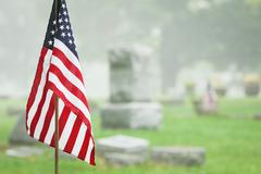 Stock Photo of American veteran flag in a foggy cemetery