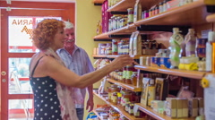 A woman taking a small box from a shelf in a store - stock footage
