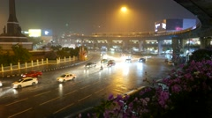 Victory Monument and Phayathai road night rainy view, Skytrain elevated railway Stock Footage