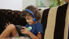 Little boy in earphones using hi-tech tablet and mumbling something to herself Stock Footage