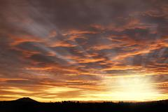Bright sunset in sky over New Zealand landscape Stock Photos