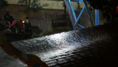 Rainfall drops shimmer in light beam, wet roof close view, night urban scene Stock Footage