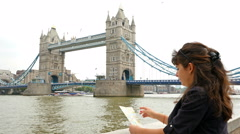 Tourist woman holding a map of London and looking at Tower Bridge Stock Footage