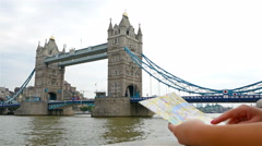 Tourist holding a map of London and looking at Tower Bridge Stock Footage