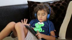 A cute little boy sits on a couch and plays with his tablet computer Stock Footage