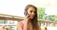Young pretty woman speaking on the phone while in caffe Stock Footage
