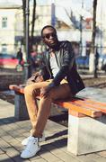 Fashion young african man wearing a sunglasses and black leather jacket sits  - stock photo