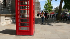 Woman looking at a map of London near a red telephone booth Stock Footage