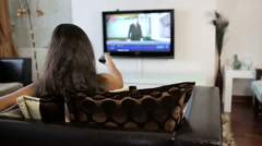 Young woman at home watching TV, turning it on, changing channels - stock footage