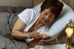 Senior woman taking her medicine at nighttime due to sickness - stock photo