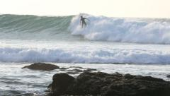 Surfer riding a large point break wave in Jeffreys Bay Stock Footage