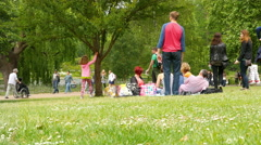 Families with children resting on the medow in a park in London Stock Footage