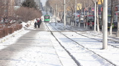 Chinese street in winter snow, tram Stock Footage