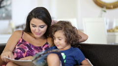 mother and son reading book together sitting on a sofa in the living room - stock footage