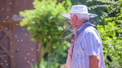 Beekeeper welcomes two visitors inside the apiary Stock Footage