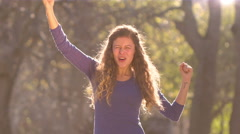 Strongly back lit woman in a park rejoices and punches the air, celebrating - stock footage