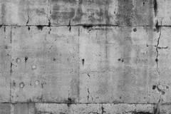 Cracks in grey concrete wall - stock photo