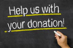 Help us with your donation written on a blackboard Stock Photos