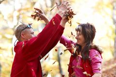 Young couple enjoying the falling leaves - stock photo