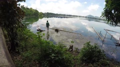Fisherman fishing on polluted lake. tracking shot Stock Footage