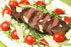Juicy flank of steak sliced with vegetables - stock photo