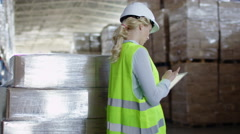 Stock Video Footage of Woman Worker in Hard Hat Working on Tablet in Logistics Warehouse