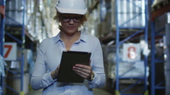 Stock Video Footage of Woman Manager in Hard Hat Walking in Logistic Warehouse. Holding Tablet PC