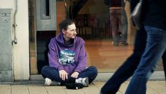 Homeless asking charity near a shop Stock Footage