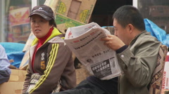 Chinese man reading newspaper Arkistovideo