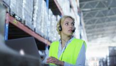 Female Worker of Logistic Warehouse is Working on Laptop. Wears Headset - stock footage