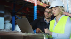 Workers of Warehouse are Working Together on Laptop. Wears White Hard Hat - stock footage