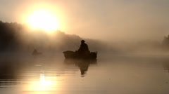 A fisherman in a boat on the morning dawn - stock footage