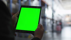 Holding Tablet PC with Green Screen in Logistic Warehouse. Mock-up. - stock footage