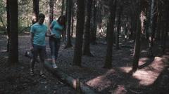 Girl Walking On Fallen Tree, Holding Her Man Stock Footage