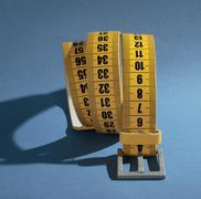 Stock Photo of Yellow meter belt slimming on a blue