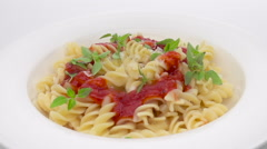 Dish with pasta and tomato souce on white background Stock Footage