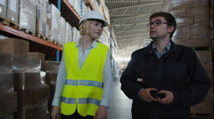 Male Worker and Female Manager are Walking through Logistic Warehouse - stock footage