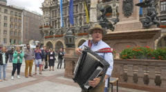 Stock Video Footage of Man with accordion entertaining the tourists in Marienplatz, Munich