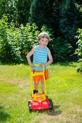 Happy small boy help with gardening with his lawn mower Stock Photos