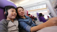 happy asian family playing and watching monitor on air plane - stock footage