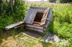 Old village wooden water well in summer day - stock photo
