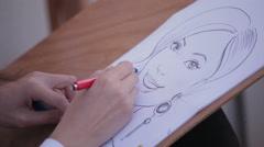 artist paints a portrait caricature of a woman, close up - stock footage
