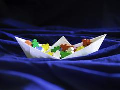 Immigration emigration migration concept, paperboat with meeples - stock photo