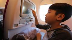 Young asian kid relaxing watching movie inside airplane. Stock Footage