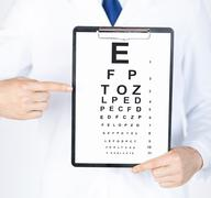 Male ophthalmologist with eye chart Stock Photos