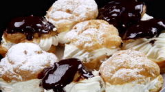 Delicious chocolate and powder flavored cream puffs - stock footage