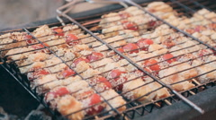 Pieces of fish and tomato on skewer roasting on a grill Stock Footage