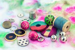 Threads and embellishments on a colorful background - stock photo