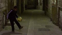a boy juggling a soccer ball in an alley filmed in - stock footage